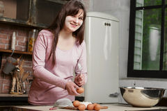 Cute brunette cooking in a home kitchen.Young beautiful smiling woman breaks an egg into the flour to the dough. Young beautiful smiling woman breaks an egg into stock images