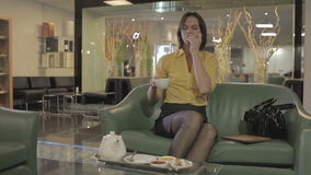 Cute brunette drink the tea and eat the sweet in the hall of the hotel. Young girl in yellow shirt sits on the green sofa in the hall of the hotel. Cute brunette stock footage