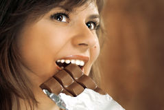 Cute brunette eats chocolate Royalty Free Stock Photos