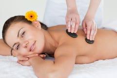 Cute brunette enjoying a hot stone massage Royalty Free Stock Photography