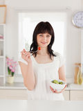 Cute brunette female eating a cherry tomato Stock Photography