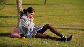 Cute brunette girl with beautiful long legs in shorts and sneakers sits on grass near tree and writes in notebook and eats apple. Cute brunette girl with stock video