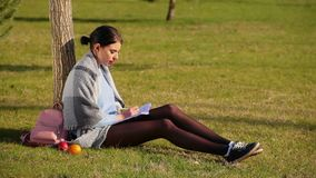 Cute brunette girl with beautiful long legs in shorts and sneakers sits on green grass near tree in park and writes in notebook. On sunny day, next to her are stock video