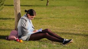 Cute brunette girl with beautiful long legs in shorts and sneakers sits on green grass near tree in park and writes in notebook. On sunny day, next to her are stock video footage