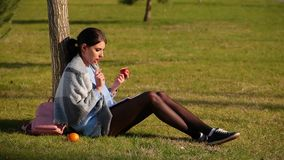 Cute brunette girl with beautiful long legs in shorts and sneakers sits on green grass near tree and writes in notebook. And eats red apple on sunny day, next stock footage