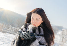 Cute brunette girl blowing snow Stock Photography