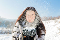Cute brunette girl blowing snow Stock Image