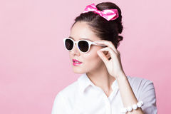 Cute brunette girl in fashionable glasses with accurate bow hairstyle Royalty Free Stock Images