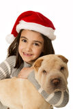 Cute brunette girl holding a Shar Pei puppy wearing a santa hat Royalty Free Stock Image