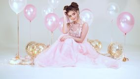 Cute brunette girl in a long light amazing pink dress, sitting on the floor in a bright garland surrounded by balls in. The studio on a white background, a stock video