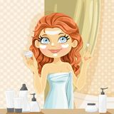 Cute brunette girl put a cream on face in the bathroom Royalty Free Stock Images