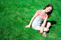Cute brunette on the green grass in summer Stock Photography