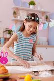 Cute brunette kid forming cookies from dough. Take it. Pleased teenager expressing positivity while preparing for festive table royalty free stock image
