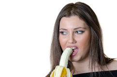 Cute brunette lady, eating a peeled banana Royalty Free Stock Photography