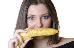 Cute brunette lady wear black shirt, holding a banana Stock Photos