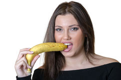 Cute brunette lady wear black shirt, holding and biting a banana Stock Image