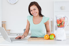 Cute brunette with a laptop and fruits Royalty Free Stock Photos