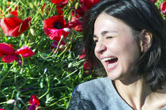 Cute brunette laughs cheerfully in a poppy field. Cute brunette laughs cheerfully against the background of a poppy field at a summer day Royalty Free Stock Photo