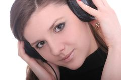 Cute Brunette Listens Music. Cute brunette listening to music over white Royalty Free Stock Photos