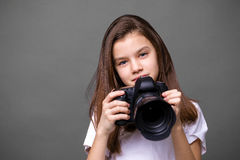 Cute brunette little girl holding an photo camera Stock Images