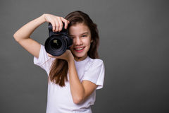 Cute brunette little girl holding an photo camera Royalty Free Stock Photo