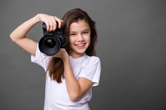 Cute brunette little girl holding an photo camera Stock Image