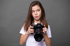 Cute brunette little girl holding an photo camera Royalty Free Stock Image