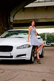 Cute brunette and luxury car Royalty Free Stock Image