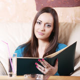 Cute brunette with menu. Cute young brunette woman with open menu Stock Image