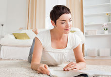 Cute brunette reading a magazine Stock Photography