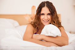 Cute brunette relaxing in a bed Stock Photography