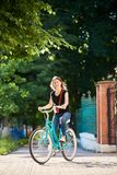 Cute brunette is riding bike on city street, summer day. A cute brunette in jeans and a T-shirt is riding a bike on a city street in a sunny summer day and Stock Photo