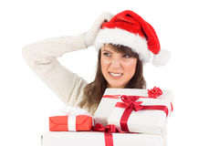 Cute brunette scratching head and holding gifts Royalty Free Stock Image