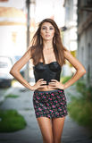 Cute brunette with short skirt posing on a city street Royalty Free Stock Photo