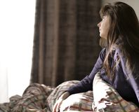 Cute brunette sits in bed after waking up, looks out the window royalty free stock photo