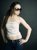 Cute brunette in sunglasses. On a dark background Stock Photos