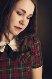 Cute brunette in tartan dress with red lips and curles. Studio portrait Royalty Free Stock Photos