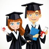Cute brunette teenage girl and boy in cap and gown graduate Stock Photography