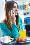 Cute brunette woman in cafe is speaking by mobile phone. In the morning Stock Image