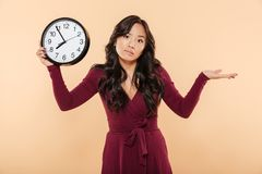 Cute brunette woman with curly long hair holding clock showing n. Early 8 being late or missing something, throwing up hand over peach background Royalty Free Stock Photography