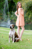 Cute brunette woman with dog, late afternoon Stock Images