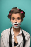 Cute brunette woman in hair curlers posing with. Cute funny  brunette woman in hair curlers wearing man shirt and tie undone posing with foam on face, isolated Royalty Free Stock Image