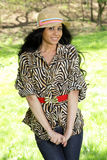 Cute brunette woman with hat. Smiling in the park. Whears an animal print blouse Royalty Free Stock Photo
