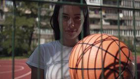 Cute brunette woman holding basketball ball looking at the camera standing behind the mesh fence at the basketball court. Portrait of brunette woman with stock video