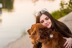 Cute brunette woman holding and embracing dog . Love to the animals, pets concept.  royalty free stock images