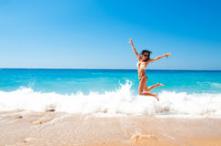 Cute brunette woman jump at sea Stock Photo