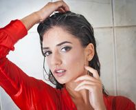 Cute brunette woman with perfect body posing in erotic pose under shower with wet hair and transparent  red shirt Stock Photography