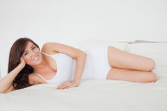 Cute brunette woman posing while lying Stock Photography