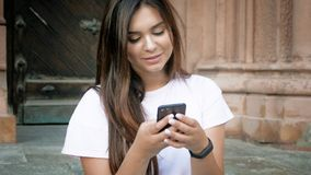 Portrait of cute brunette woman sitting on stone stairs and typing message on mobile phone stock photography