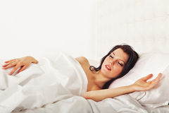 Cute brunette woman sleeping in white bed Stock Photo